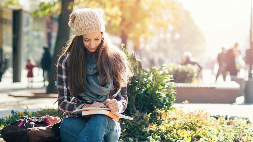young woman reading on bench