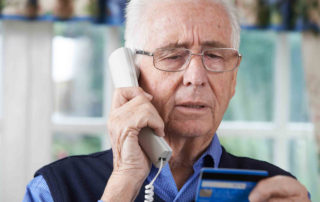 senior on phone while looking at credit card
