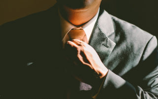 man in a suit adjusting his tie