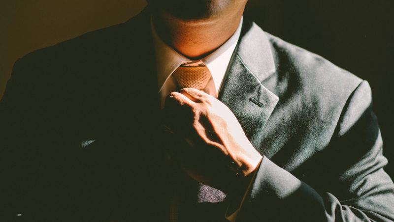 man in a suit adjusting his tie